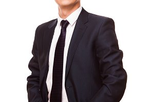 Young handsome businessman in black suit is standing straight, full length portrait isolated on white background