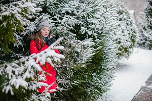 Girl winter stands next to a fir-trees
