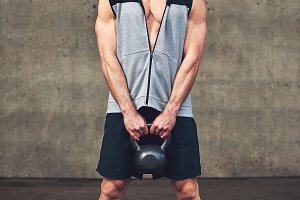 Young strong sportive male holding heavy kettlebell