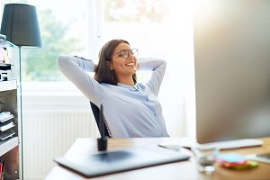 Happy woman with arms folded behind head