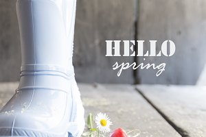 hello spring text, daisy and boots on a vintage table,