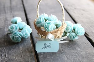 Hello March. Rustic still life, roses and tag, vintage table