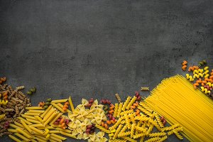 Various types of pasta - spaghetti, penne, fusilli, colored vege