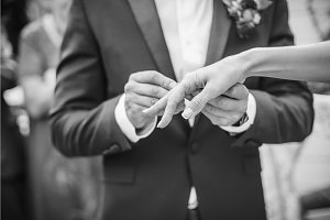 The groom wears a ring for bride. black and white photo