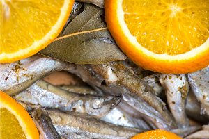 fried fish dish with sliced orange and bay leaf. selective focus macro shot with shallow DOF