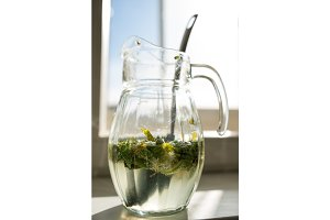 Carbonated soda water or juice with lime and mint in a glass jug on the window background