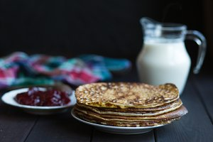 Homemade pancakes with raspberry jam on a dark wooden table. Shrove Tuesday