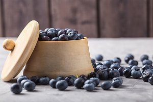 garden blueberries in a wooden pot and vintage wooden spoon