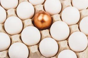 Gold egg between white eggs