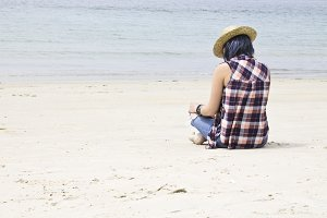 Woman with straw hat and book on the beach