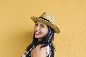 Woman with straw hat on yellow wall