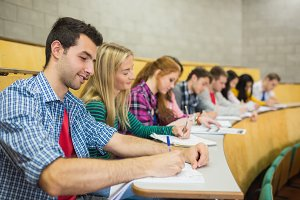 Students writing notes in a row at lecture hall