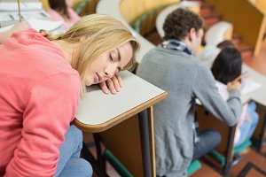 Asleep female with students sitting in lecture hall