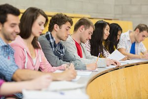 Students writing notes in a row at the lecture hall