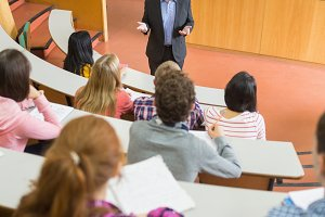 Elegant teacher with students at the lecture hall