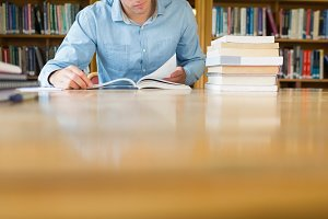 Mid section of a mature student at library desk