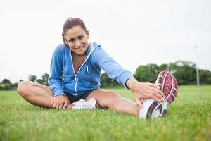 Portrait of a sporty stretching her leg on the grass