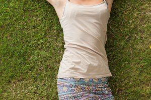 Young woman resting on grass at the park