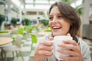 Cheerful student drinking coffee in the cafeteria