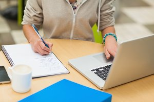 Mid section of a female student doing homework by laptop
