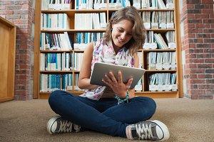 Female student against bookshelf using tablet PC on the library floor