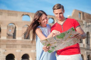 Young tourist couple traveling on holidays outdoors smiling happy. Caucasian family with map over Coliseum background