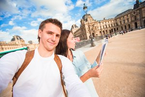 Happy young couple with map of city taking selfie in Paris outdoors
