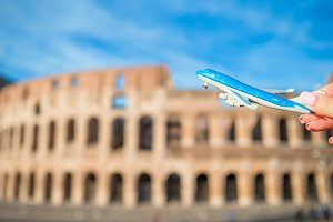 Closeup model airplane on Colosseum background. Italian european vacation in Rome. Concept of imagination.
