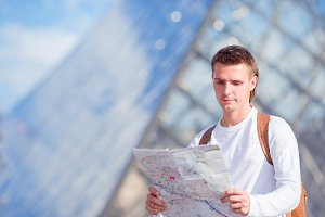 Young tourist man with map in european city outdoors