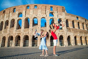 Happy family in Europe. Parents and kids in Rome over Coliseum background.