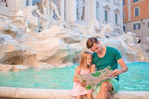 Family with touristic map near Fontana di Trevi. Father and adorable girl on italian holiday in Europe.