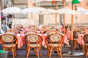 Summer empty open air restaraunt in Pisa in Italy. Closeup wineglasses on the table