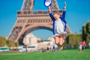 Adorable happy little girl in Paris background the Eiffel tower during summer vacation