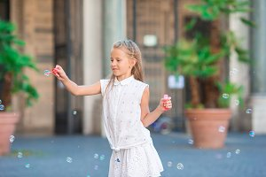 Adorable little girl blowing soap bubbles in european city. Portrait of caucasian kid enjoy summer vacation in Italy