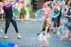 Adorable little girl blowing soap bubbles in Trastevere in Rome. Happy kid enjoy summer vacation in Italy