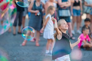 Adorable little girl blowing soap bubbles in european city. Happy kid enjoy summer vacation in Italy