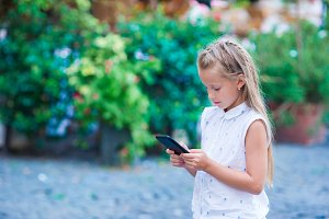 Adorable toddler girl with smart phone in Europe city outdoors