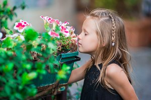 Little adorable girl smelling colorful flowers outdoors