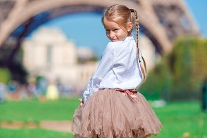 Adorable little girl near the Eiffel tower during summer vacation in Paris