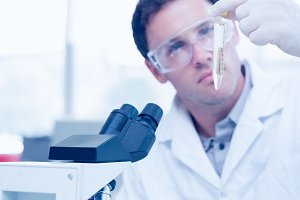 Scientific researcher looking at test tube while using microscope in lab