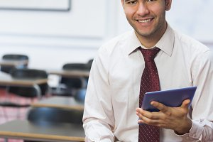 Smiling teacher with tablet PC in the class room