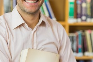Smiling mature student against bookshelf in library