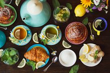 Cups of herbal tea with lemon and mint leaves, ginger root and croissant on the wooden background, top view