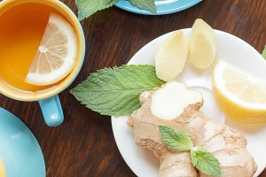 Cup of herbal tea with lemon and mint leaves, ginger root and croissant