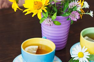 Cups of herbal tea with camomile and mint leaves on the wooden background