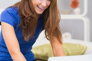 Smiling woman using laptop at home