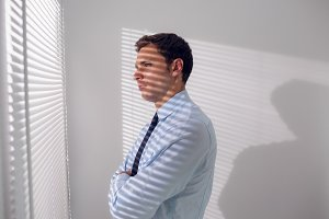 Businessman peeking through blinds in office