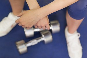Low section of a tired woman with dumbbells in gym