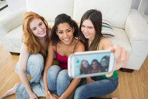 Friends photographing themselves with smartphone at home