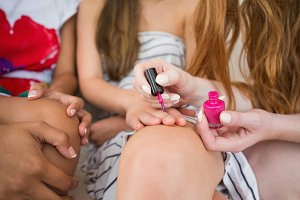 Mid section of a young woman painting friends nails